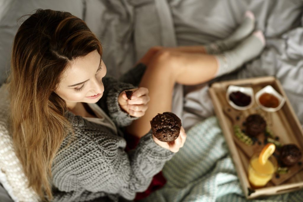 Woman eating cupcake in bed